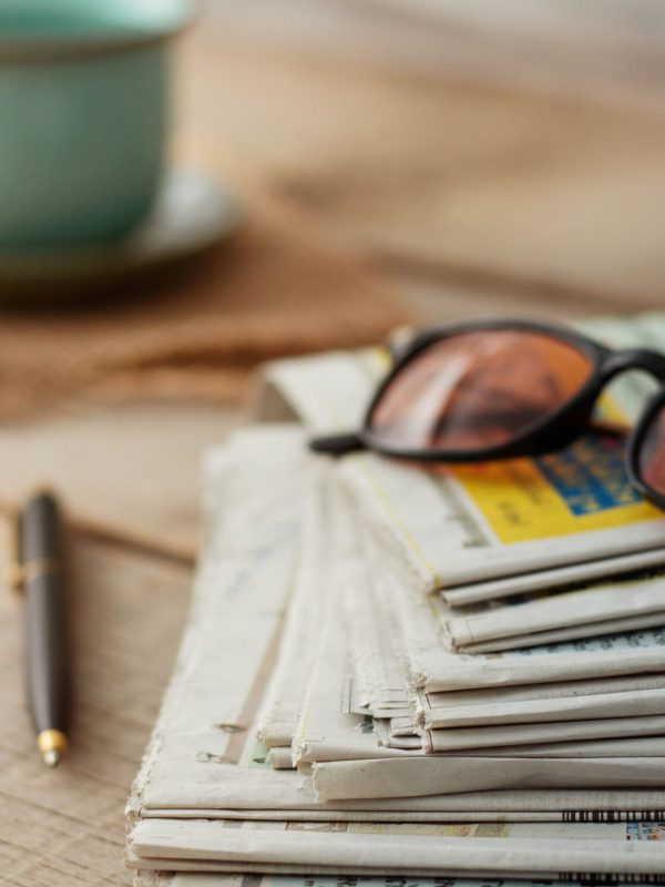 Newspapers and glasses on wooden floors.